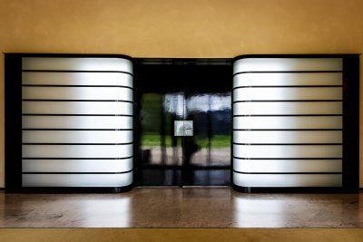 Les boîtes à lumière de l'entrée encadrant la double porte, qui constitue l'écran noir d'un cinéma.
