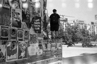 Manifestant sur la place Baquedano et la statue couverte d'affiches et de slogans