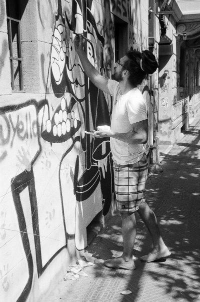 Artiste en train de tager un mur près de la place Baquedano