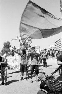Manifestant portant un drapeau se faisant photographier